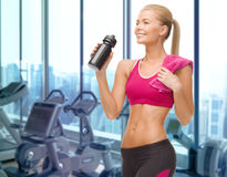 Happy woman drinking water from bottle in gym Stock Image
