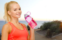 Happy woman drinking water from bottle outdoors Royalty Free Stock Images
