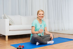 Happy woman drinking water and exercising at home Stock Photos