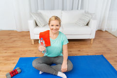 Happy woman drinking water and exercising at home Stock Image