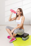 Happy woman drinking during workout royalty free stock image