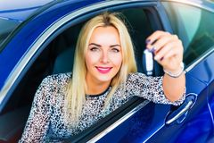 Happy woman driver holding auto keys in her car Royalty Free Stock Images