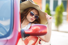 Happy woman driving a red compact car Royalty Free Stock Images