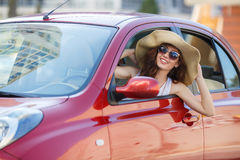 Happy woman driving a red compact car Royalty Free Stock Image