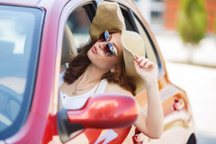 Happy woman driving a red compact car Royalty Free Stock Photography