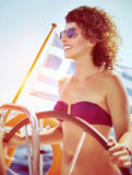 Happy woman driving sailboat Stock Images