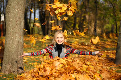 Happy woman drop up leaves in autumn park Stock Images