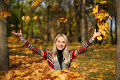 Happy woman drop up leaves in autumn park Stock Photography