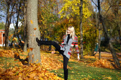 Happy woman drop up leaves in autumn park Stock Photos