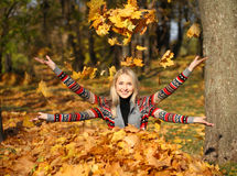 Happy woman drop up leaves in autumn park Royalty Free Stock Image
