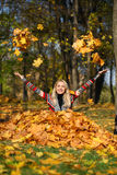 Happy woman drop up leaves in autumn park. Portrait close up of young beautiful woman, on background autumn park Stock Image