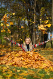 Happy woman drop up leaves in autumn park Royalty Free Stock Images