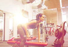 Happy woman with dumbbell flexing muscles in gym Stock Image