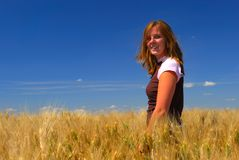 Happy Woman in Durum Wheat. Pretty young woman stands in durum wheat field on gorgeous summer day Royalty Free Stock Photo