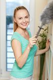 Happy woman with duster cleaning at home Stock Images