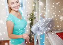 Happy woman with duster cleaning at home Royalty Free Stock Photos
