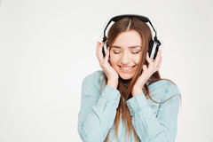 Happy woman in earphones listening to musinc with closed eyes Royalty Free Stock Photos