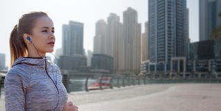 Happy woman with earphones running over dubai city Stock Photos