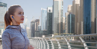 Happy woman with earphones running over dubai city Stock Photo