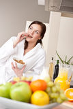 Happy woman eat cereals for breakfast in kitchen Royalty Free Stock Photography