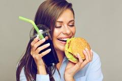 Happy woman eatin American classic fast food. stock photo