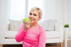 Happy woman eating apple at home Stock Photo