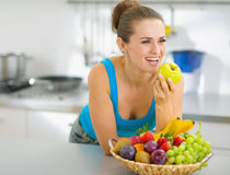 Happy  woman eating apple in kitchen Stock Photos