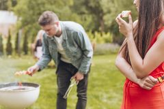 Happy woman eating bread while her friend grilling shashliks. Happy women eating bread while her friend grilling shashliks photo concept stock photo