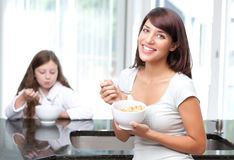 Happy woman eating breakfast cereal with daughter. An attractive, happy, hispanic women eating healthy breakfast cereal with daughter Royalty Free Stock Photography