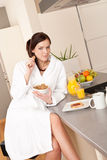 Happy woman eating breakfast in kitchen Royalty Free Stock Image