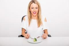 Happy woman eating broccoli Royalty Free Stock Image