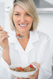 Happy woman eating cereal for breakfast Stock Photos