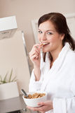 Happy woman eating cereals in kitchen Stock Images
