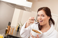 Happy woman eating cereals in kitchen Royalty Free Stock Image