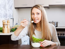 Happy woman eating cottage cheese Stock Images