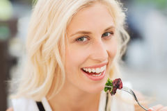 Happy woman eating dinner at restaurant terrace. People, holidays, food and leisure concept - happy woman with fork eating squid for dinner at restaurant terrace Stock Photography