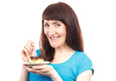 Happy woman eating fresh baked cheesecake. Happy smiling woman eating fresh baked piece of cheesecake Royalty Free Stock Image