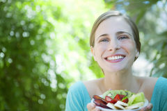 Happy woman eating fruit salad Stock Photography