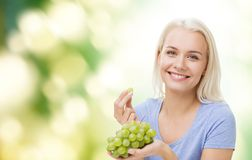 Happy woman eating grapes Stock Images