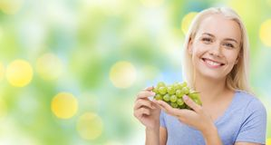 Happy woman eating grapes Stock Photo
