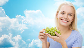 Happy woman eating grapes over sky Stock Images