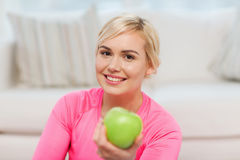 Happy woman eating green apple at home Royalty Free Stock Image