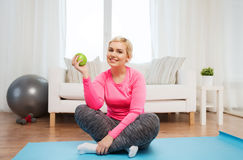 Happy woman eating green apple at home Stock Photos