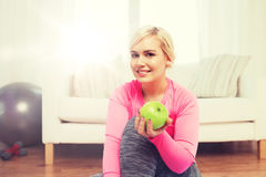Happy woman eating green apple at home Stock Images