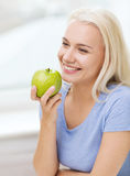 Happy woman eating green apple at home Stock Photography