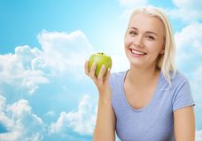 Happy woman eating green apple over sky Stock Images