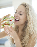 Happy woman eating large sandwich in house Stock Photo