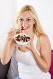 Happy Woman eating muesli. Happy blonde woman eating muesli with fruit at breakfast Stock Photography