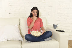 Happy woman eating popcorn watching television at sofa couch happy excited enjoying movie Stock Image