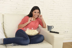 Happy woman eating popcorn watching television at sofa couch happy excited enjoying movie Royalty Free Stock Photo